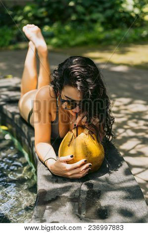 Beautiful Young Woman In Bikini And Sunglasses Drinking Tropical Cocktail Near Swimming Pool