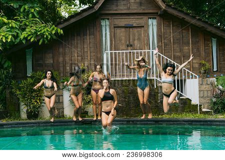 Attractive Young Women In Swimwear Jumping In Swimming Pool At Tropical Resort