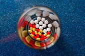 Colorful pills and medicines in glass plate on blue background. Different pills and another drugs capsules for illegal doping manipulations. Pharmacy antibiotic and antidepressant. poster