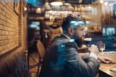 Bearded man rest in restaurant with beer glass. Businessman with long beard drink in cigar club. Beer time. serious bar customer sit in cafe drinking ale. Date meeting of hipster awaiting in pub. poster