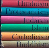 A stack of colorful books with different religions on the spine which includes:  Islam, Catholicism, Buddhism, Judaism, Islam, Catholicism, Buddhism poster