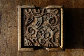 Close-up Of Wooden Tea Coasters With Carved Indian Patterns In Case On A Vintage Wooden Tabletop, Li