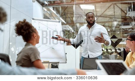 Young Afro American Businessman Pointing At White Blackboard And Explaining New Project To His Colle