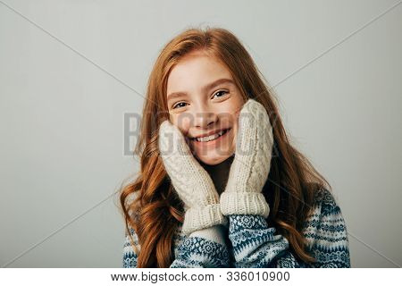 The Girl In A Sweater Smiles, Warming Her Face With Gloves On Her Hands. Warm Knitted Gloves Were Ve