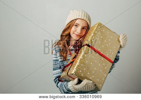 Teenager In A Knitted Hat, Sweater And Gloves. A Girl Hugs Her Christmas Present From Her Parents. H