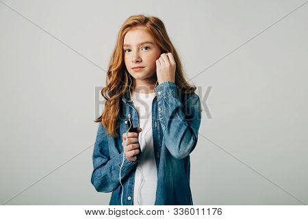 Red-haired Girl Listens To Music In Small Headphones. She Does Not Want To Talk To Her Parents And T
