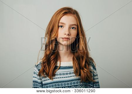 A Young Red-haired Girl In A Blue Sweater Looks At The Camera. A Girl With A Worried Video Is Trying