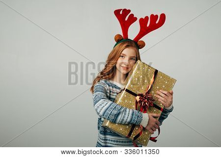 Red-haired Girl Hugs Her Present From Parents At Christmas. The Blue-eyed Lady Is Happy About The Ne