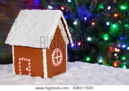 The Hand-made Eatable Gingerbread House, Snow Decoration, New Year Tree With Garland In Background