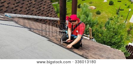 Moscow, Russia - August 21, 2019: Worker Does The Installation Of The Roof Of The House. Installatio