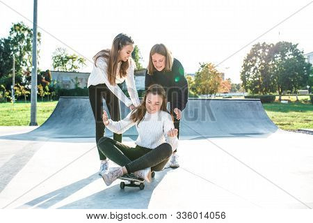 Three Teenage Girls Teenagers Ride A Skateboard, Happy Have Fun Playing And Laughing, In The Summer