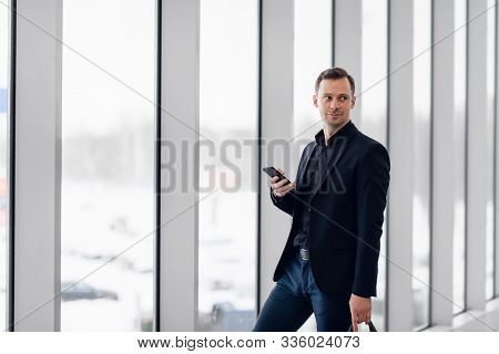 Business Man Using Mobile Phone App In Airport. Young Business Professional Man Texting Smartphone W