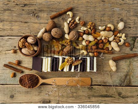 Bitter And Milk Chocolate, Nuts And Other Sweets On A Wooden Table.