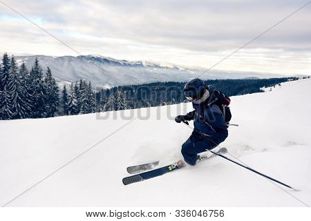 Skier Inclining Turning On Snow-capped Mountain Peak. Backcountry Skier Doing Professional Skiing Te