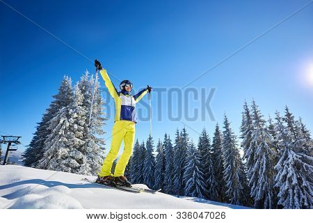 Low Angle View Of Rejoicing Young Woman On Skis With Hands Up With Ski Poles. Wooded Snow-covered Sl