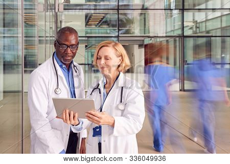 Male And Female Doctors Having Informal Meeting In Modern Hospital Looking At Digital Tablet