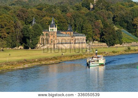 A Distant View Of The Old Waterworks At Dresden Nearby The Elbe River With A River Boat And People W