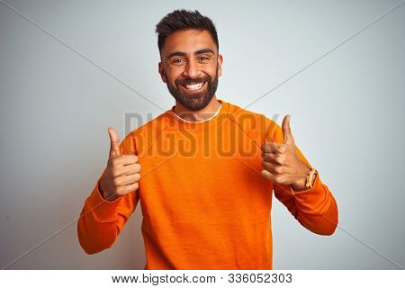 Young indian man wearing orange sweater over isolated white background success sign doing positive gesture with hand, thumbs up smiling and happy. Cheerful expression and winner gesture.