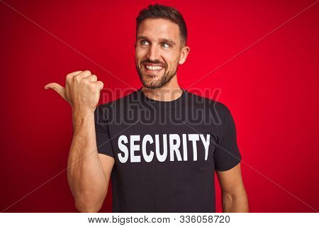 Young safeguard man wearing security uniform over red isolated background smiling with happy face looking and pointing to the side with thumb up.