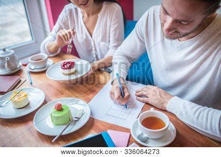 Businessman Making Notes While Revising Desserts For Their Menu