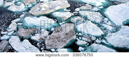 Iceberg and ice from glacier in arctic nature landscape on Greenland. Aerial drone image of icebergs in Ilulissat icefjord. Affected by climate change and global warming.