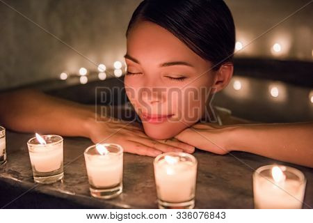 Beautiful young woman relaxing in jacuzzi hot tub at spa. Attractive female tourist is enjoying in water. Smiling woman with eyes closed is pampering herself during vacation. poster