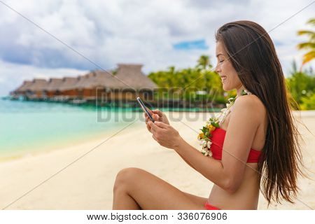 Travel vacation woman using smartphone texting relaxing on beach at luxury hotel resort in Tahiti, French Polynesia.