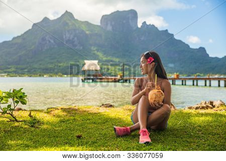 Bora Bora tourist woman relaxing on beach drinking fresh coconut water by Otemanu mount in landscape. French Polynesia travel vacation.
