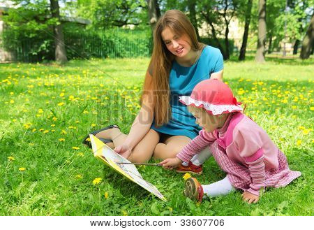 Girl And Mother Reading The Book In Spring Park
