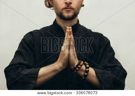 A Man In Black Shirt Sitting Folded Palms Together, Doing Yoga. Hands Folded In Prayer. Hands Togeth