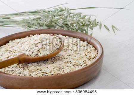 Oatmeal In A Brown Ceramic Bowl With A Wooden Spoon On A Background Of Green Ripe Ears Of Oats On A