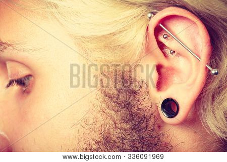 Stretched Lobe Piercing, Grunge Concept. Pierced Man Ear With Black Plug Tunnel. Industrial And Rook