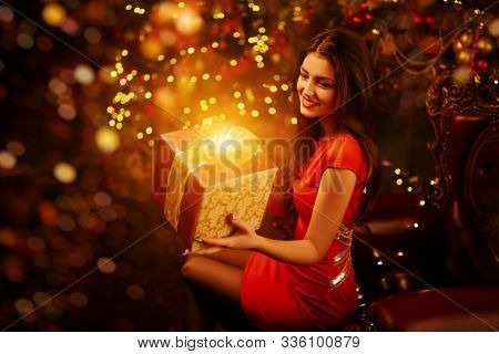 Christmas and New Year concept. Beautiful happy girl celebrates Christmas in the fairy Christmas interior with lights around. Christmas tree and fireplace in the background.