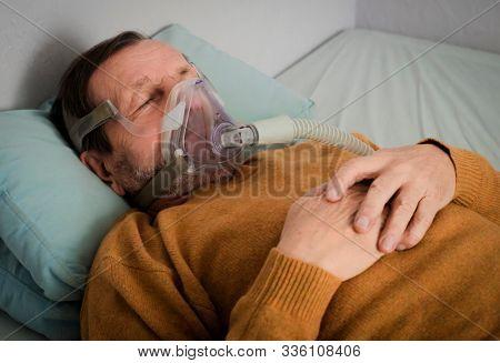 Elderly Man Lying On Bed With Sleeping Apnea And CPAP Machine