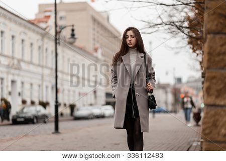 Attractive European Young Woman In An Elegant Coat In A Black Skirt With A Trendy Leather Bag Walks