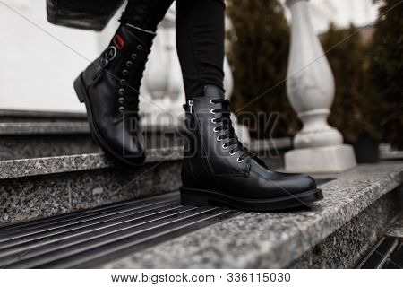 Fashionable Young Woman Stands On The Stone Steps In The City In Black Trendy Leather Lace-up Boots