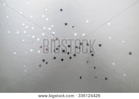 Silver Stars On A Silver Background. Christmas And New Year Background Of Silver Confetti Stars.