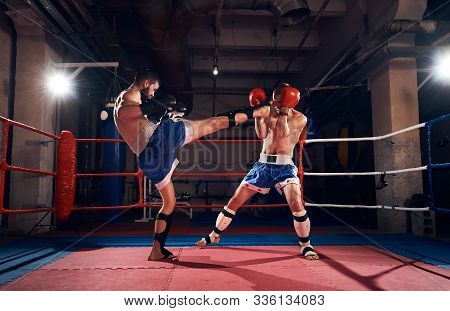 Two Athlete Kickboxers Practicing Kickboxing In The Ring At The Health Club