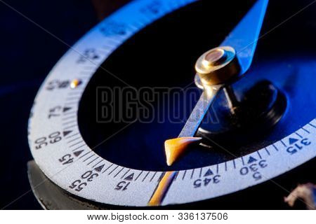 Vintage Magnetic compass compass on blue background. Macro photo.