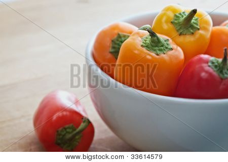 Colorful mini sweet peppers in a white bowl