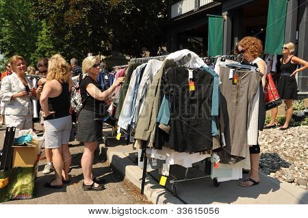 Women shop for clothes at garage sale