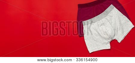 Mens Underwear, Red Burgundy And Gray Underpants On Red Background Flat Lay Top View Copy Space. Fas