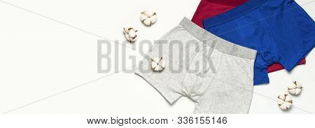 Mens Underwear, Set Of Multi-colored Underpants And Cotton Flowers On White Background Flat Lay Top