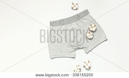 Mens Underwear, Gray Underpants And Cotton Flowers On White Background Flat Lay Top View Copy Space.