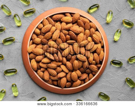 Almonds As A Source Of Omega Fatty Acids In A Round Plate And Yellow Gelatin Capsules Scattered On A