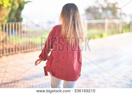 Young beautiful woman wearing red jacket on backview standing at the town street