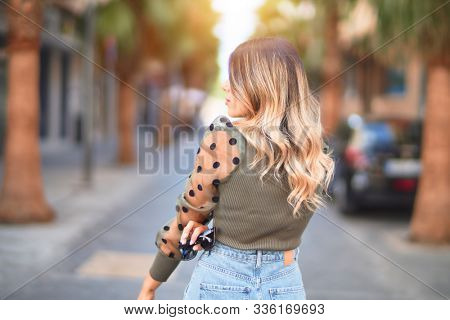 Young beautiful woman wearing fashion clothes. Standing and walking on backview at town street