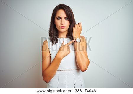 Young beautiful woman wearing dress standing over white isolated background In hurry pointing to watch time, impatience, looking at the camera with relaxed expression