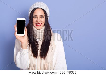 Young Woman Showing Display Of Mobile Cell Phone With Blank Screen, Stands Smiling Isolated Over Blu
