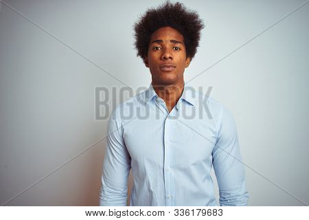 Young african american man with afro hair wearing elegant shirt over isolated white background with serious expression on face. Simple and natural looking at the camera.